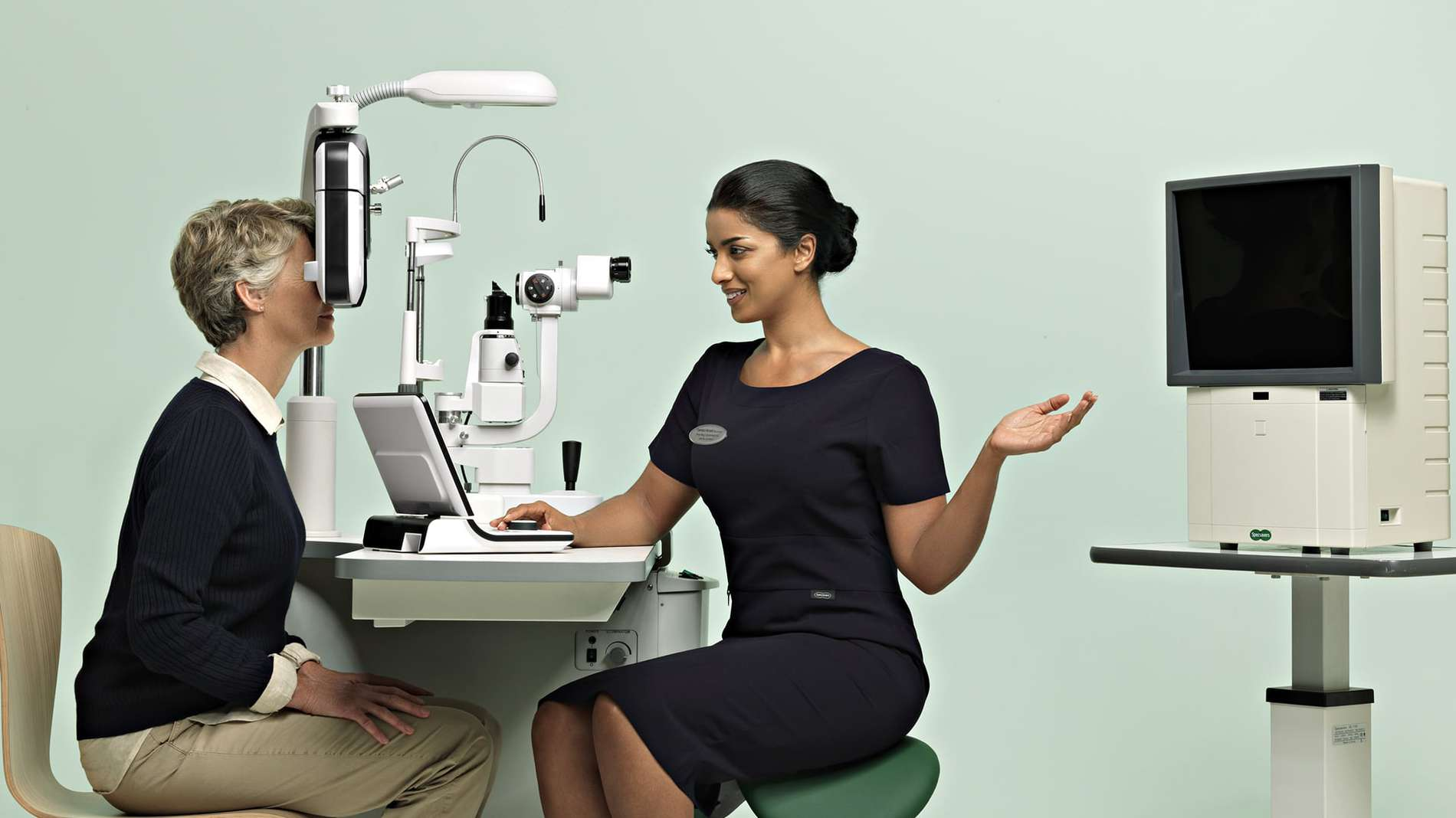 A Specsavers' eye doctor conducting a routine examination of a patient.