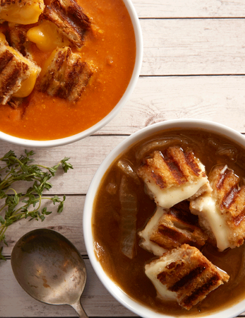 Grilled Cheese Tomato Soup topped with grilled cheese croutons and French Onion Soup topped with provolone cheese croutons.
