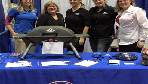 Farmers Agent Jennifer with 4 female staff members at a booth at an RV show