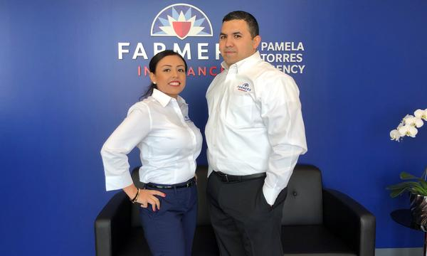 2 agents posing in front of blue wall displaying Farmers logo
