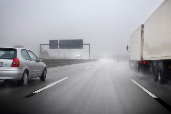 Cars driving on a rainy and foggy highway