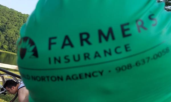 Farmers Insurance, The Gerald Norton Agency logo on a swimming cap.