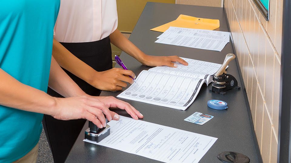 The UPS Store associate stamping a notarized document