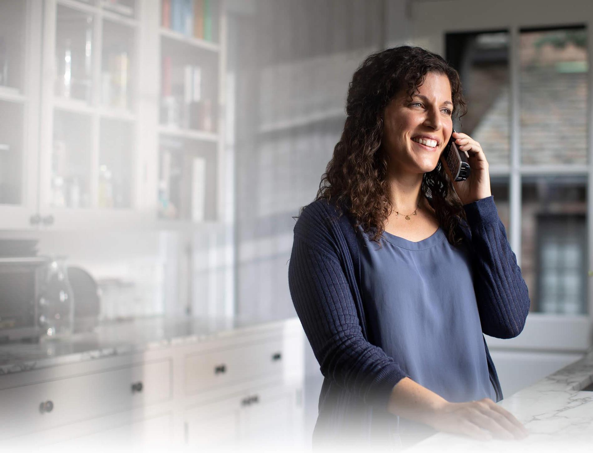 Foto de una mujer parada en la cocina hablando con un teléfono inalámbrico y usando una conexión de Suddenlink Voice