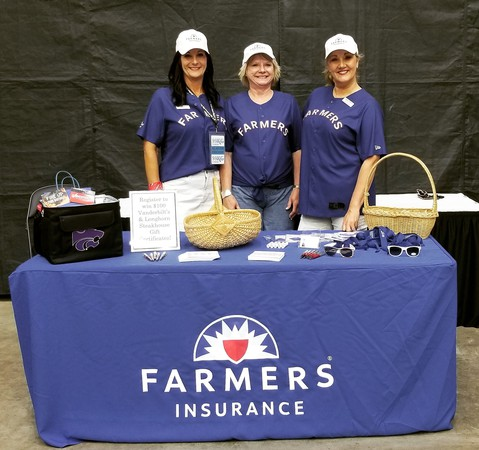 Three people standing behind a Farmers table