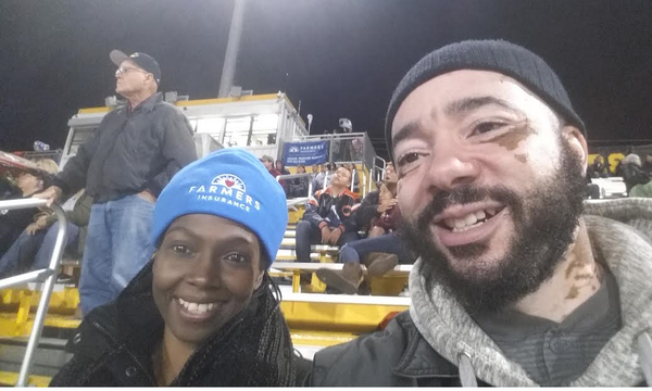Agent Felicia Traylor wearing a Farmers Insurance winter cap, with a man in the stands of a sporting event.