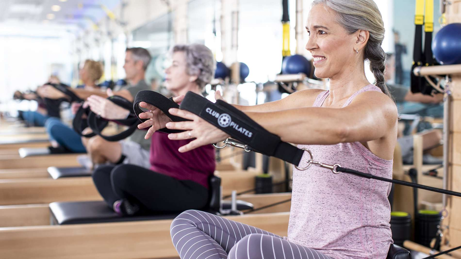 A line of Club Pilates members do stretches with bands.