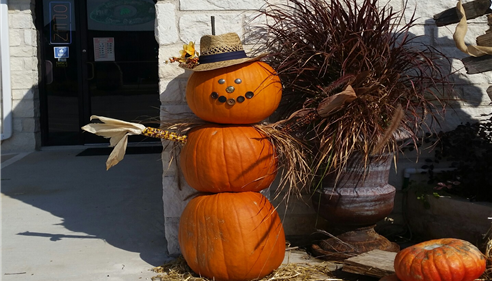 A snowman made with three pumpkins and a hat.