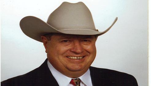 Agent Arthur Carlson in a suit and cowboy hat