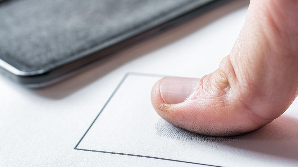 A person's thumb pressing down on ink fingerprinting paper card