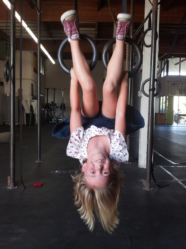 Girl hanging upside down on gymnastics rings