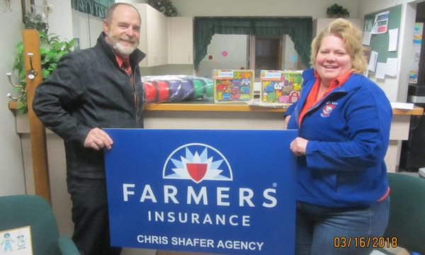 Agent Chris Shafer in a classroom standing with a woman holding a Farmers Insurance sign.