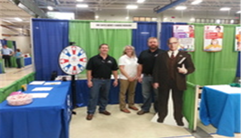 Four people are standing in front of a Farmers Insurance booth at a large expo or event