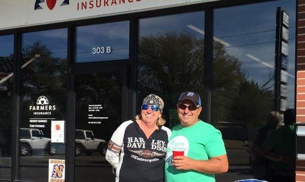 Photo of man and women in front of front of Farmers Insurance building.