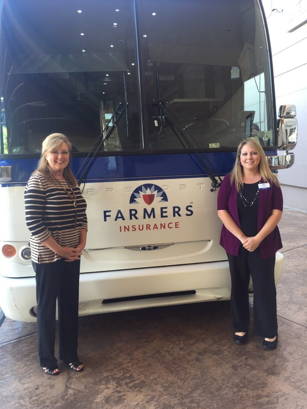 2 people standing in front of a farmers bus