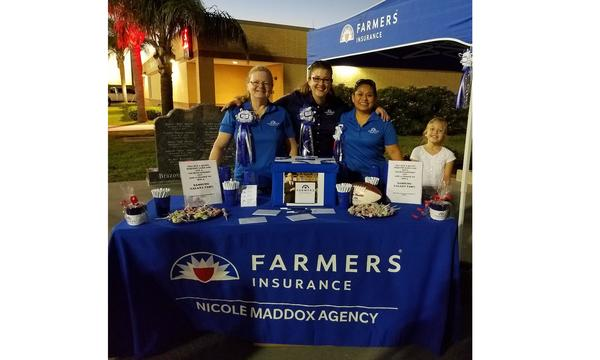 A group of people stand behind a farmers booth