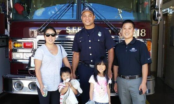 Agent and family standing with a fireman in front of a firetruck