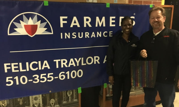 Agent Felicia Traylor standing with a man in front of a Farmers Insurance banner with her name and phone number on it.