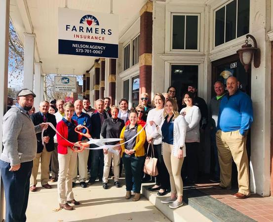 Photo of Farmers Agent cutting a ribbon for their business' ribbon cutting ceremony, surrounded by other friends and supporters.