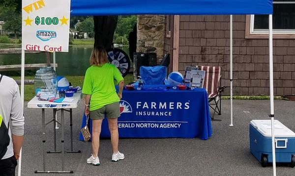 A visitor standing in front of a Farmers Insurance promotional table for the Gerald Norton Agency.