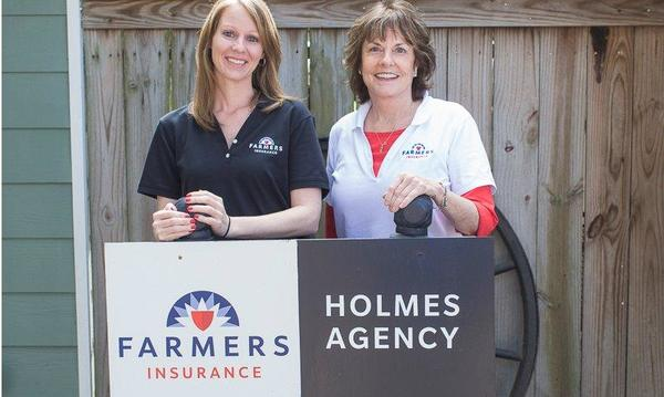 Agent Martha and a woman standing in front of farmers sign.