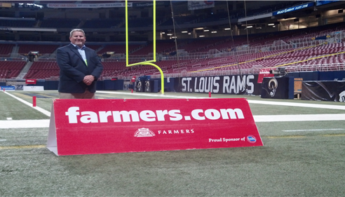 Agent poses with Farmers sign