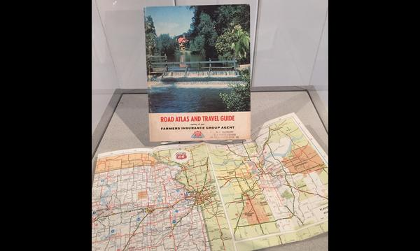Historic road map with Road Atlas and Travel Guide book behind the map.