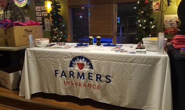 Photo of booth with white cloth with Farmers logo on it.