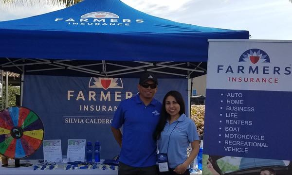 Two people posing in front of a blue Farmers booth.