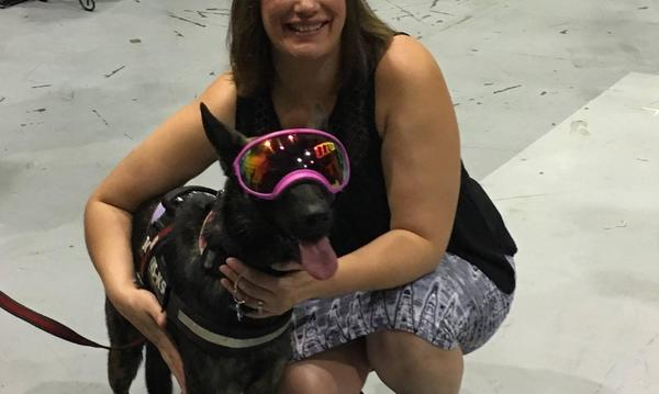 A girl posing with a dog wearing goggles.