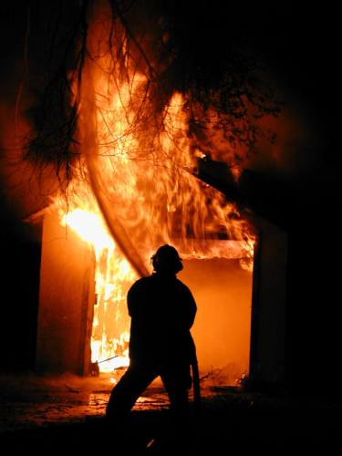 Silhouette of fireman fighting a fire