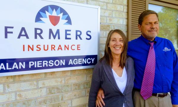 Agent standing with wife in front of agency sign