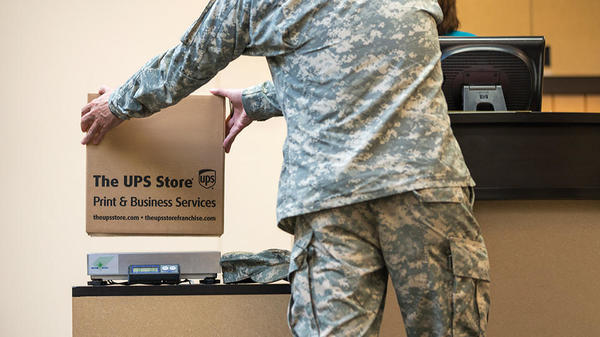 military officer dropping off the ups store shipment package at counter