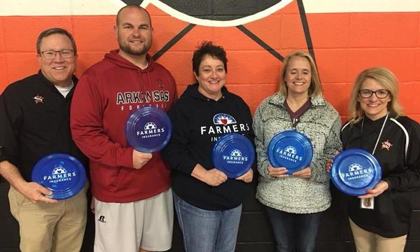 Agent Ruth Steely and her staff standing with a local gym teacher, holding frisbees.