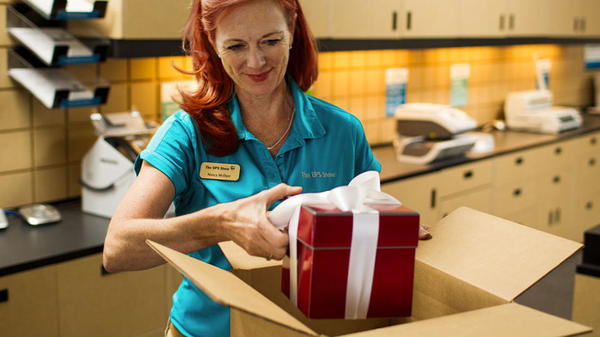 Employee shipping red gift with white bow