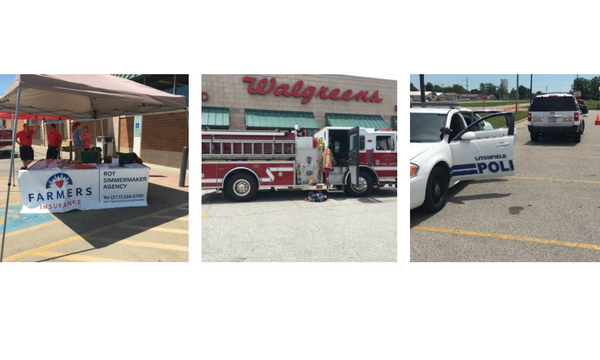 Photo of a Farmers agent table, a fire truck, and police cars in a Walgreens parking lot.