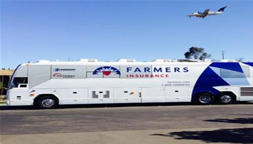 A large Farmers branded bus sits in a parking lot