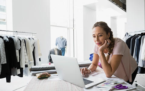 Woman on laptop looking for small business owner insurance