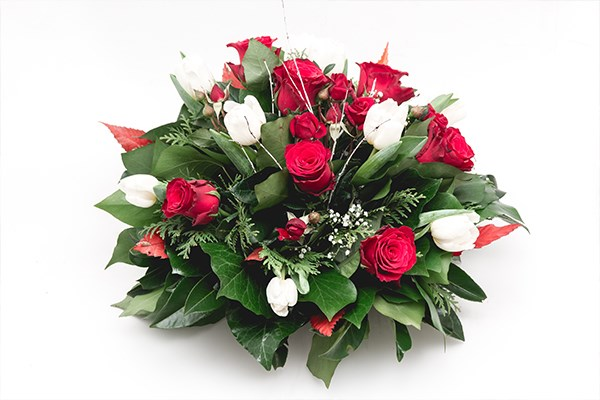 A posy of red roses and white lilies arranged into a classic floral tribute