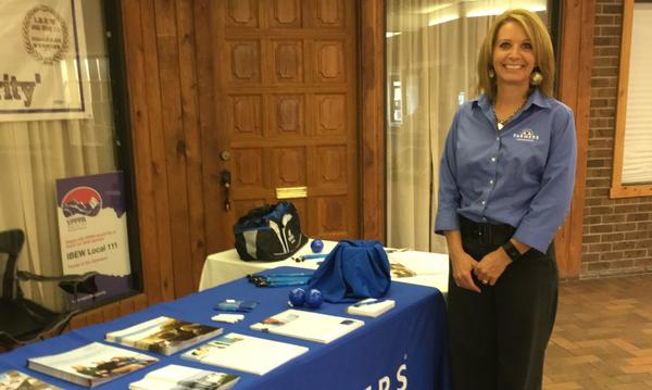 Agent Debbie Montgomery standing next to Blue Farmers Table