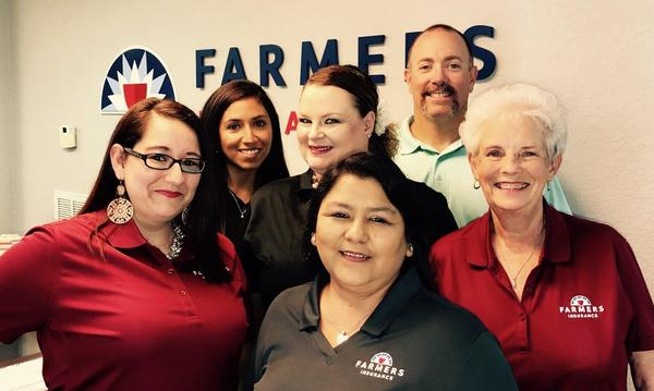 Agent with 5 female members of his staff, standing in front of the Farmers Insurance logo