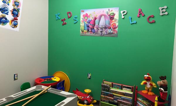 A kids playroom with a trolls poster on the wall and toys on the floor