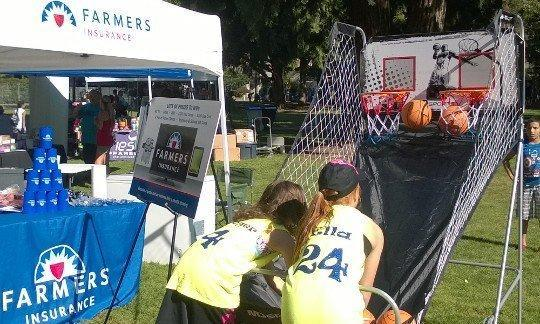 Two children shooting basketballs into hoops located next to a Farmers insurance tent