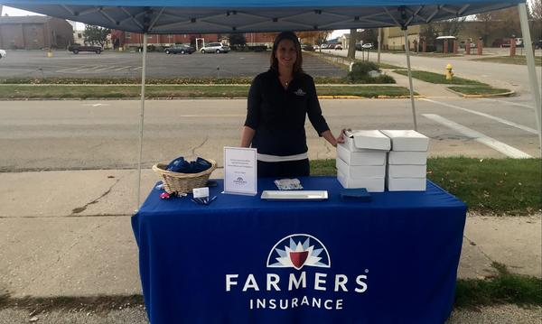 Agent standing outside behind a Farmers insurance table