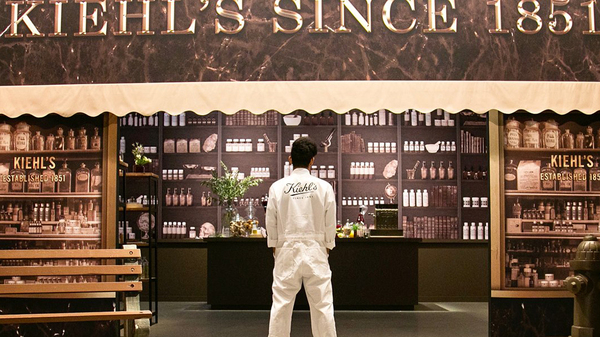 "A man dressed in all white stands with his back to the camera wearing a white jacket that says ""Kiehl's"" on the back"