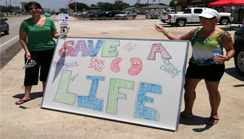 two female staff members with a save a life sign