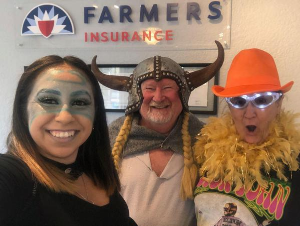 Two men and a woman in costumes standing by a Farmers® Insurance sign