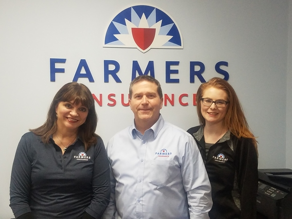 Staff in front of the farmers logo
