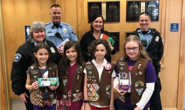 Agent with police officers and girl scouts, holding cookies