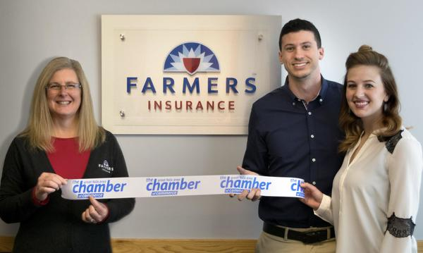 The team are holding up a little ribbon in front of a Farmers Insurance logo on the wall